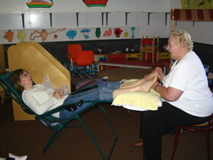 Tina Thatcher being given a reflexology treatment by Mary Gilhooly